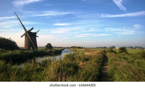 Old windmill by the water on the Norfolk Broads in East Anglia England on a Summer afternoon with blue sky and a man walking in the distance