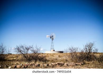 Old Windmill In Desert In Clear Sky