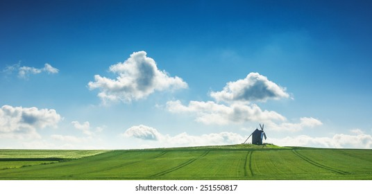 Old  windmill in the field and blue sky with clouds