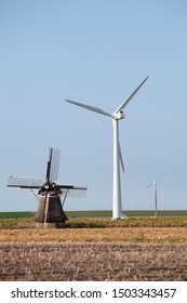 old windmill and modern turbines together in agricultutre landscape of friesland in the netherlands