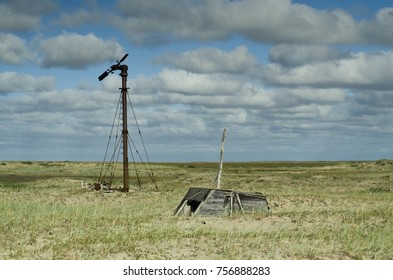 Old windmill on an abandoned meteorological station in the Arctic tundra on the coast of the Arctic Ocean