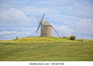 Old windmill on a farm on the top of a hill in Normandy, France