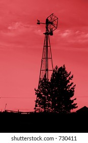 An old windmill on the prairie with red sky