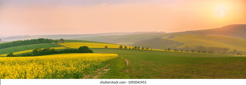 Old windmill at sunset. Spring landscape with rolling hills, Moravian fields panorama, Czech Republic