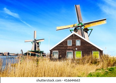 Old windmill in Zaanse Schans, traditional village in Netherlands, North Holland, high grass, blue cloudy sky