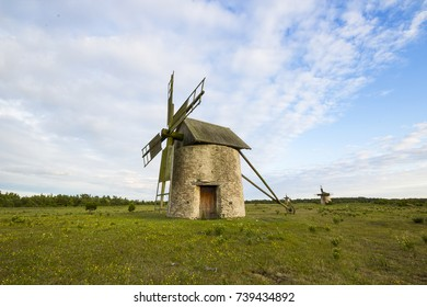 Old windmills on the open field during sunset