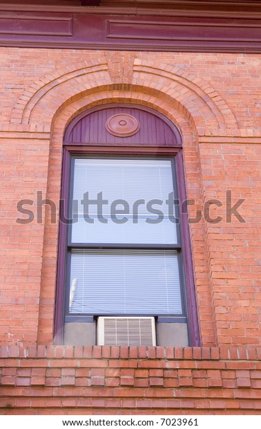 An old window with an air conditioner unit mounted