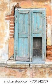 Old window with broken shutters