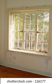 Old window in haunted house with peeling white lead based paint