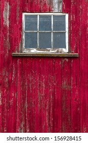 Old window on abandoned red barn with textured old split wood