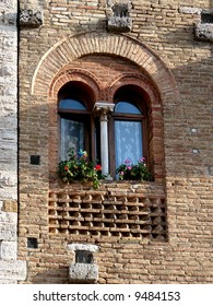 An old window on house in La Cisterna square in city of San Gimignano. Very good example of medieval construction with archs and columns.
