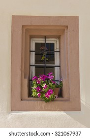 Old window with red flowers on the bavarian house, Germany