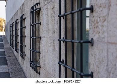 Altes Fenster mit rostig gefälschten Bars auf weißem Hintergrund. Die Fenster sind in einer Reihe mit massiven schwarzen Balken.