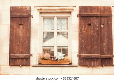 old window with shutters and flowers