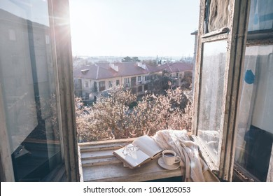 Old window with the view from inside into blooming tree. Opened book, cup of tea or coffee, glasses and knitted sweater on windowsill. Cozy spring weekend concept.