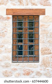 Old window with wooden frame and black lattice on the background of the white stone wall