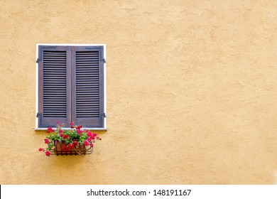 Old window with wooden shutters on yellow stucco wall and copy space