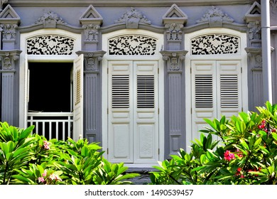 Old windows with antique  wooden shutters on Singapore shop house framed by frangipani tree in  historic Duxton Hill, Singapore.