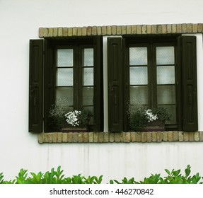old windows with carved frames in the southern town with shutters and flowers on the windowsill
