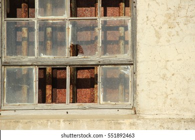 Old windows on ruin house, with broken glass and rusty iron bars