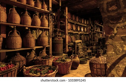 Old wine barrels, casks and bottles in wine-cellar