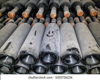 Old wine bottles in the cellar, wine cellar with wine at the winery, dust on wine bottles, smile painted on the dust