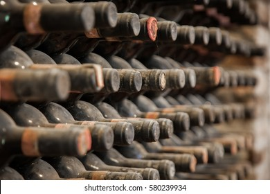 old wine bottles covered with dust and cobwebs are in the wine cellar