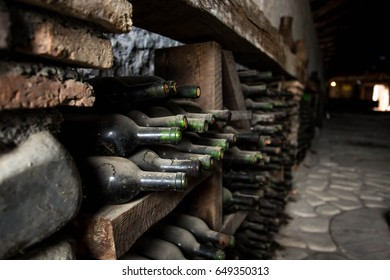 Old wine cellar with many glass bottles and rustic wooden shelves on stone walls of rural storage of winery or restaurant