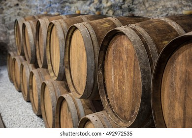 An old wine cellar with oak barrels full of red wine