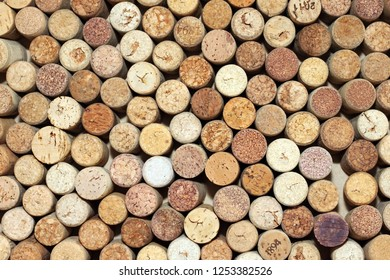 old wine corks from red wine among used corks from white wine and from sparkling wine as abstract brown cork background