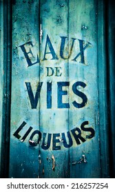 """Old wine and spirit cellar sign. Text in French """"Eaux de vies, liqueurs"""" meaning """"Brandy, liqueurs"""". Toned photo."""