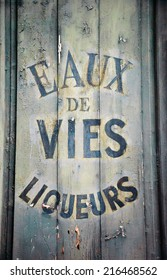 """Old wine and spirit cellar sign. Text in French """"Eaux de vies, liqueurs"""" meaning """"Brandy, liqueurs""""."""