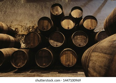 Old winery with wooden barrels full of port wine inside. Dark cellar for winemaking, Portugal.