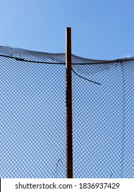 old wire fence made of thin wire against the blue sky, fencing private territories and private property with passive means of protection, the wire rustes and is used on high fences and fences for