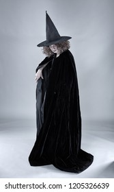 Old witch in black cape and hat against gray background