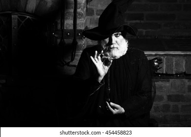 Old wizard with pendulum in costume and hat for Halloween black and white on kitchen background