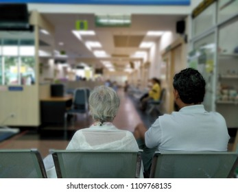 old woman and adult man sit on gray stainless chair waiting medical and health services to the hospital,patients waiting treatment at the hospital,blurred image of many people