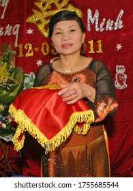An old woman in Ao dai traditional dress with happy face in wedding of her son