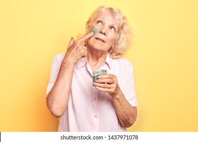 old woman applies an anti-aging facial mask with a finger.close up portrait. isolated yellow background. studio shot.beauty care, wellness, wellbeing.