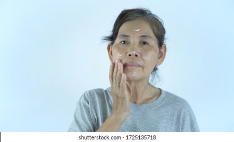An old woman applying cream on a white background.
