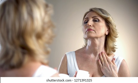 Old woman applying nourishing cream on neck and decollete zone, anti-age care