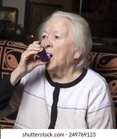 Old woman with asthma inhaler at home