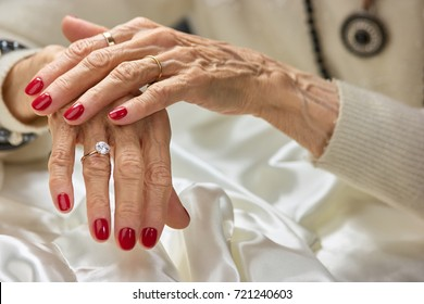Old woman beautiful hands with rings. Female aged hands with red nails wearing luxury golden rings. Womens aristocratism and well-being.