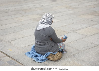 Old woman beggar sitting begging money from  French people and foreigner travlers at walkway for go to visit and travel at courtyard of Cathedrale Notre Dame de Paris in Paris, France