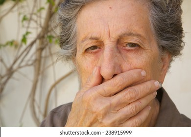 An old woman between 70 and 80 years old closed the mouth with a hand expressing that someone does not let her to tell anything