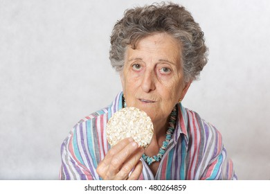 Old woman between 70 and 80 years old is eating whole grain dried bread