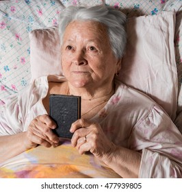 Old woman with Bible lying in bed at home