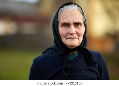 Old woman in black outdoor in the countryside