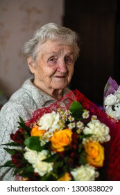 An old woman with a bouquet of flowers.