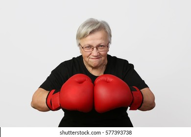 Old woman in boxing gloves with resolute strong facial expression on gray background
